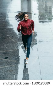 frontal photo of a sportswoman running wearing a red windbreaker, black leggings and white trainers under the rain in the city