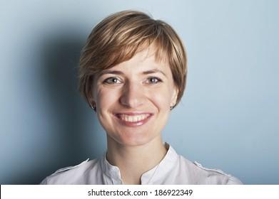 frontal portrait of a beautiful joyful woman, studio shot on blue