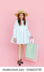 Frontal portrait of a cheerful attractive little girl in elegant white dress and straw hat, holding shopping bag isolated on a pink background. Vertical view.
