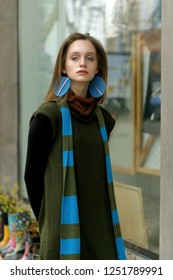 Frontal portrait of a girl who stands at the window of a vintage clothing store. She is dressed in a boho style: a green jumpsuit and a long blue scarf.