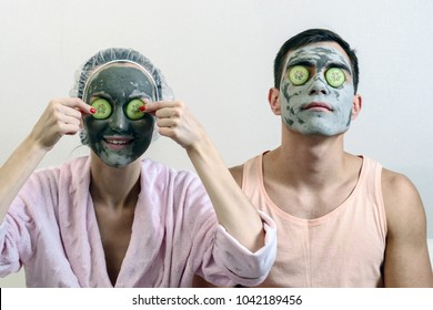 Frontal portrait of a married couple with clay masks on his face and cucumbers in front of him. Spa at home. skin care.