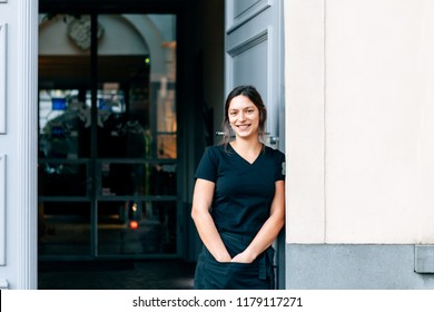 frontal portrait of a smiling girl bar tender wearing a black uniform and standing outside the entrance