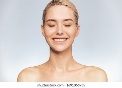 Frontal portrait of a young smiling girl with closed eyes. Face close-up of a blonde girl with bright emotions. Skin and body care concept.