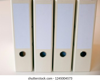 Frontal slightly downwards view to a serie of four paper binders folders with a blank front with room for text standing on a clean white shelf