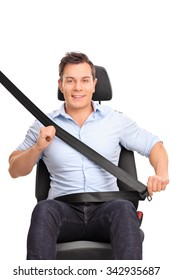 Frontal vertical shot of a young man sitting on a car seat and fastening his seat belt isolated on white background