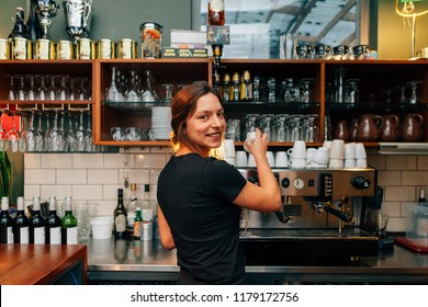 frontal view of beautiful girl bartender working behind the bar