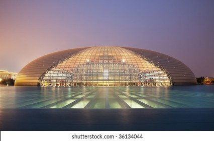 Frontal view of Beijing National Grand Theater shot with water reflections against a clear blue night sky.