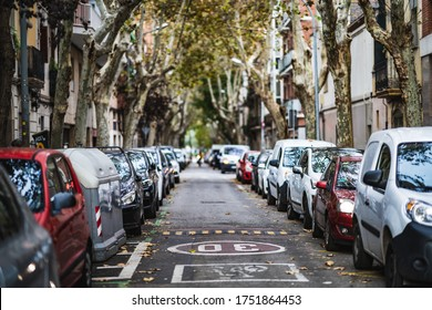 Frontal view of a city street with cars parked on both sides