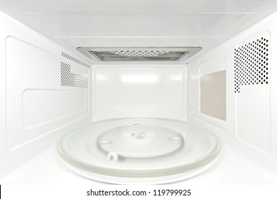 Frontal view inside white, empty clean microwave oven interior