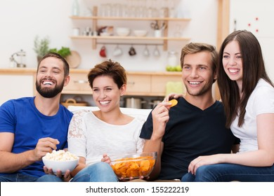 Frontal view of a laughing group of diverse young friends sitting on a sofa watching television and eating snacks