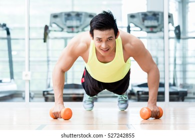 Frontal view of male bodybuilder doing pushups while holding dumbbells in his hands