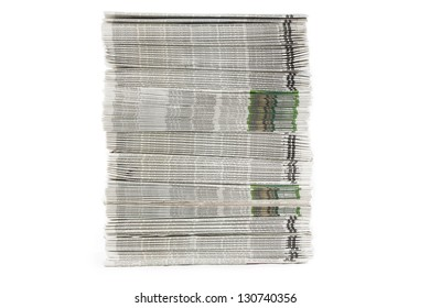A frontal view of neatly stacked freshly printed newspapers