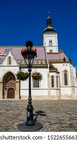 Frontal view of St. Mark's Church in Zagreb, Croatia, with an ornamental gas lamp.