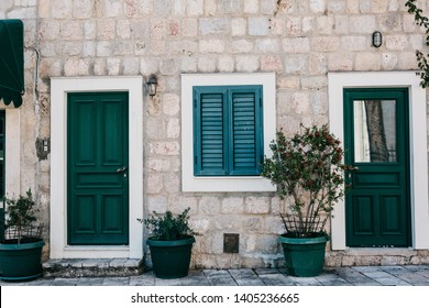 Frontal view of a stone residential building with entrance door and windows with shutters and decorated with plants.