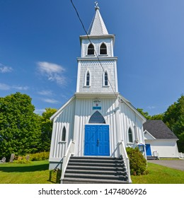 Frontal view of the white and blue Grace Anglican church, Arundel, Quebec, Canada