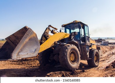 The front-end loader carries crushed stone to fill the road. Special equipment for the repair of the road.