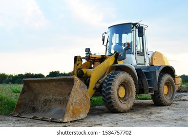 Front-end loader working on construction site during the renovation of the road. Laying or replacement of underground storm sewer pipes. Installation of water main, sanitary sewer, storm drain systems