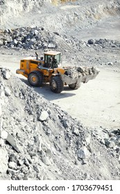 Front-end loader works in a quarry against the backdrop of limestone debris, close-up.