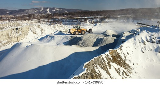 Front-end shovel loader on the background of the relief of a snow-covered stone quarry, panorama.