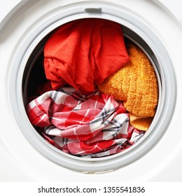 front-loading washing machine or washer full of dirty laundry or colored washables