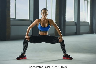 Frontview of attractive woman with athletic body doing sitting up and downs in spacy gym. Having sturdy muscles, healthy body and tanned skin. Looking strong, fit, feeling good. Wearing sportswear.
