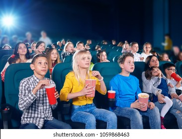 frontview of little exited children watching interesting movie in cinema hall. Boys and girls look very emotional and happy. schoolmates wearing colorful clothes,eating popcorn, drinking fizzy drinks.