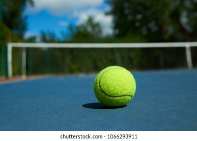 Frontview of yellow bright tennis ball is lying on on blue carpet of opened court during sunny day. Made for playing tennis. Contrast image with satureted colors. Concept of tennis outfit photografing