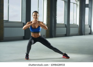 Frontview of young sporty girl with athletic body doing fallouts in gym. Having sturdy muscles, healthy body and tanned skin. Looking strong, fit, feeling good. Wearing comfortable stylish sportswear.
