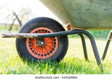 frontwheel of wheelbarrow standing on the lawn of a garden - close up - with blurry background