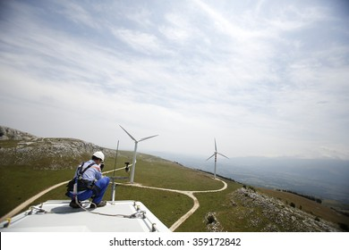 FROSOLONE, ITALY - 29 JULY 2014: A worker checking an anemometer, used to measure the wind speed, located on the top of a wind turbine standing on a hillside at a wind farm in Frosolone.