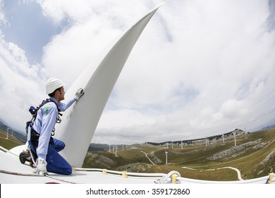 FROSOLONE, ITALY - 29 JULY 2014: A worker wearing a safety harness and hard hat checks the top of a wind turbine standing on a hillside at a wind farm in Frosolone.
