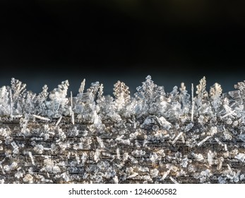 Frost crystals forming beautiful  geometrical shapes on wood surface against black background