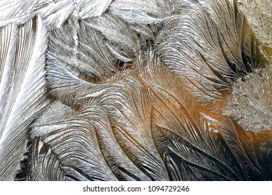 Frost draws on glass of the windows complex,amazing,beautiful patterns,drawings,pictures,lace. Festoons of the multicolored lights.Freezing patterns melt from solar heat.