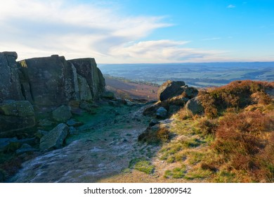 Frost lies on the ground in the shadow of a small gritstone cliff on Curbar Edge