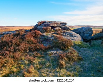 Frost lingers on the grass and frens that surround a gritstone rock formation on Curbar Eege in the Derbyshire Peak District.