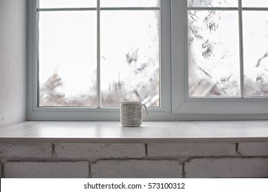 ?ozy and frost winter still life:  hot tea or coffee  on windowsill against snow landscape from outside.