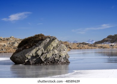 Frosted alpine lake in autumn, with skyline mountains background, Valle Brembana, Italy)