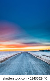 Frosted Asphalt Country Open Road Through Winter Snowy Fields And Meadows At Sunset Or Sunrise. Landscape In Belarus Or European Part Of Russia