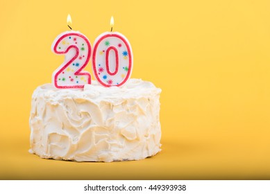Frosted cake with the number 20 lighted candles