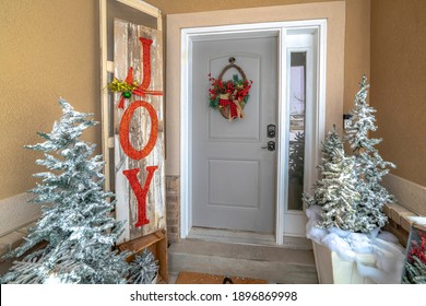 Frosted christmas trees and holiday decorations at the festive entrance of home