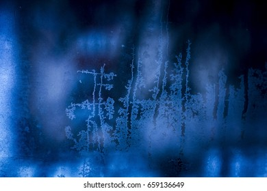 Frosted glass closeup. Beautiful Abstract winter holiday background. Ice texture on the window
