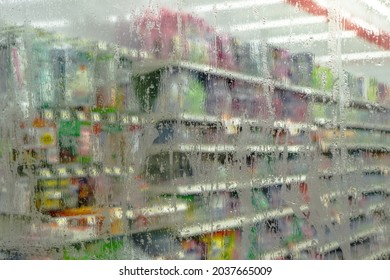 Frosted glass island of convenience store stained with raindrops