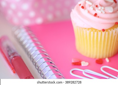 A frosted pink cupcake on a notebook with paperclips, a pen, and a ribbon.