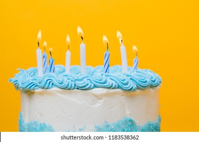 Frosted white cake with blue decorations and candles