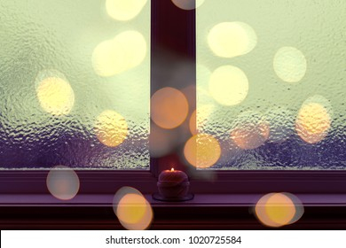 Frosted window in dark evening light, with a candle burning on a windowsill.