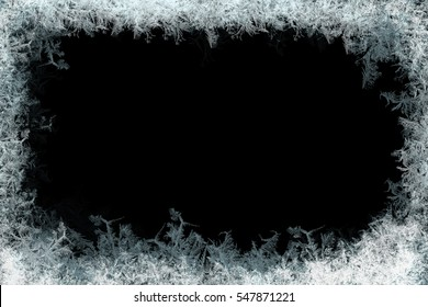 Frostwork. Decorative ice crystals on a window in form of a frame on black matte background