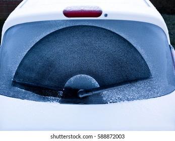 Frosty car window; rear window of car covered in early morning frost