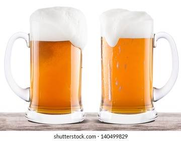 Frosty glass of light beer on a wooden table isolated on a white background