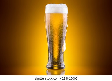 Frosty glass of light beer on a colored background