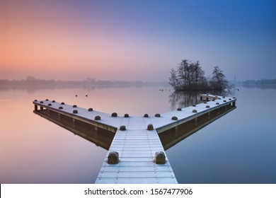A frosty jetty on a beautiful foggy morning in winter. Photographed in the Amsterdamse Bos (Amsterdam Forest) at sunrise.